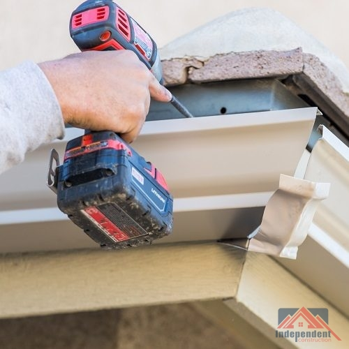 A Picture of a Man Attaching Aluminum Gutter To Fascia.